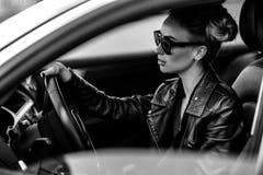 Dana det utomhus- fotoet av den sexiga härliga kvinnan med mörkt hår i svart läderomslag och solglasögon som poserar i lyxig auto Fotografering för Bildbyråer