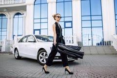 Dana det utomhus- fotoet av den sexiga härliga kvinnan med mörkt hår i svart läderomslag och solglasögon som poserar i lyxig auto Royaltyfria Bilder