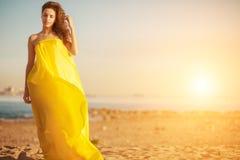 Dana flickan i en lång klänning mot en sommarsolnedgångbakgrund Royaltyfria Bilder