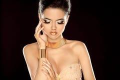 Dana fotoet av den härliga brunettkvinnan som poserar i guld- jewe Royaltyfria Foton