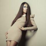 Dana fotoet av den unga sinnliga kvinnan i beige klänning Royaltyfria Bilder