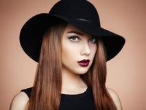 Dana fotoet av den unga storartade kvinnan i hatt posera vatten för bakgrundsflicka arkivfoton