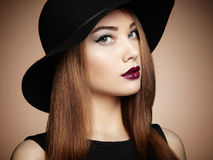 Dana fotoet av den unga storartade kvinnan i hatt posera vatten för bakgrundsflicka royaltyfria foton