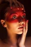 Dana konstbegreppet. Skönhetkvinnan vänder mot med målat rött maskerar Royaltyfria Bilder