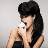 Dana kvinnan med den moderna frisyren med det vita äpplet Royaltyfri Bild