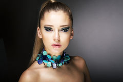 Lyx. Ursnygg moderiktig kvinna med turkoshalsbandet Royaltyfri Foto