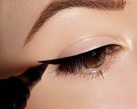 Dana kvinnan som applicerar eyeliner på ögonlocket, ögonfrans Använda makeupborsten, formsvartlinje Yrkesmässig sminkkonstnär arkivbilder