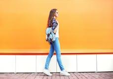 Dana kvinnan som går i stad över den färgrika apelsinen royaltyfria bilder