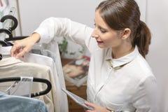 Dana kvinnan som väljer ett stycke för den nya samlingen med siffran arkivfoto