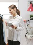 Dana kvinnan som väljer ett stycke för den nya samlingen med siffran Arkivfoton