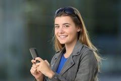 Dana kvinnlign som använder en telefon och ser dig på gatan royaltyfria foton