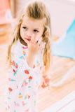 Dana lilla flickan som poserar i klänning mot den färgrika väggen arkivfoto