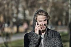 Dana macho le med smartphonen i tillfällig tröja Lycklig grabb i huvsamtal på mobiltelefonen på soligt utomhus- Skäggig man s royaltyfria bilder