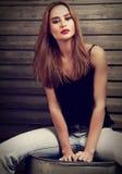 Dana makeupkvinnan med lång hårstil i jeans och rött fotografering för bildbyråer