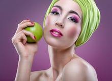 Dana modell med härlig rosa makeup och göra grön äpplet Royaltyfri Fotografi