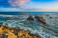 Dana Point Sunset. Breathtaking ocean view a sunset with clouds in the sky and rock formations along the shore, Dana Point, California stock photography