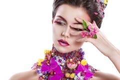 Dana skönhetkvinnan med blommor i hennes hår och runt om hennes hals Perfekt idérik smink- och hårstil arkivbild