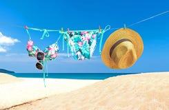Dana sommarbaddräktbikinin, solglasögon och den stora hatten på rep För sommarbikinin och ställde den stilfulla dräktstranden in  Arkivfoto