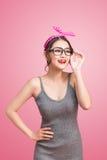 Dana ståenden av den asiatiska flickan med solglasögon som står på rosa färger Royaltyfri Bild