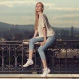 Dana ståenden av den blonda kvinnan Jeans och gymnastikskor Arkivbild
