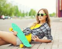 Dana ståenden av den nätta kalla flickan i solglasögon med skridskon Arkivbilder