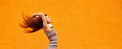 Dana ståenden av den nätta le kvinnan i solglasögon som dansar med hörlurar mot den orange väggen Konditionarmband Arkivfoto