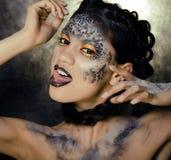 Dana ståenden av den nätta unga kvinnan med idérikt smink som en orm Arkivbilder