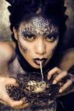 Dana ståenden av den nätta unga kvinnan med idérikt smink som en orm Arkivbild