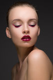 Dana ståenden av den perfekta kvinnan med röda eller rödbruna kanter och magentafärgad pilbotten av ögon på mörker - grå bakgrund Arkivbild