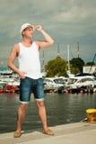 Dana ståenden av den stiliga mannen på pir mot yachter Royaltyfri Bild
