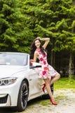 Dana ståenden av den unga kvinnan i den eleganta klänningen som är utomhus- i cabr Arkivfoto
