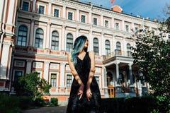 Dana ståenden av den ursnygga flickan med blått färgat hår länge Den härliga aftoncoctailklänningen Royaltyfri Bild