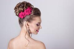 Dana ståenden av en härlig attraktiv flicka med höga försiktiga eleganta frisyrer för ett aftonbröllop och ljust smink med flöde Royaltyfri Bild