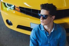 Dana ståenden av stiligt mansammanträde nära den moderna gula sportbilen Mode modernt annonsering Arkivfoto