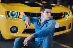 Dana ståenden av stiligt mansammanträde nära den moderna gula sportbilen Mode modernt annonsering Royaltyfria Bilder