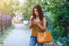 Dana stadsståenden av den stilfulla hipsterkvinnan med mobiltelefonen, makeup, långa brunetthår, tyck om semestern i Europa Arkivfoton
