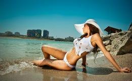 Dana ståenden av den unga sexiga brunettflickan i bikini och blöta t-skjortan på stranden Royaltyfria Bilder