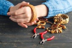 Danande av handgjorda smycken Boxas med pärlor och glass hjärtor på gammal träbakgrund Handgjord tillbehör Arkivfoto
