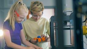Danandeprocessen av en vetenskaplig apparat bar ut vid en pojke och en flicka arkivfilmer