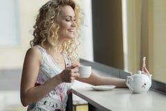 Danandesjälvstående för ung kvinna på hennes digitala kamera för smart telefon, medan sitta i kafé under lunchavbrott Royaltyfri Foto