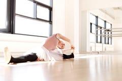 Dançarino de bailado em esticar o exercício no assoalho Fotos de Stock Royalty Free