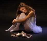 Dançarino de bailado novo que descansa no assoalho Fotos de Stock Royalty Free
