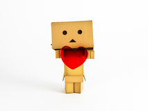 Danbo holding a heart. Cute Danbo character lovingly holds out a red heart Royalty Free Stock Image