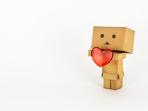 Danbo holding a heart. Cute Danbo character lovingly holds out a red heart Royalty Free Stock Images