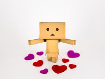 Danbo standing amongst hearts. Cute Danbo character posing adorably with outstretched arms surrounded by hearts.  Shallow depth of field Royalty Free Stock Image
