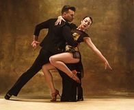 Dance ballroom couple in gold dress dancing on studio background. stock images