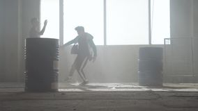Dance battle of two street dancers in an abandoned building near the barrel. Hip hop culture. Rehearsal. stock footage