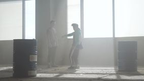Dance battle of two street dancers in an abandoned building near the barrel. Hip hop culture. Rehearsal. stock video
