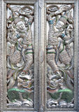 Dance of Buddhist monk on head of dragon. Metallic door with carved decoration in traditional Buddhist temple Stock Image