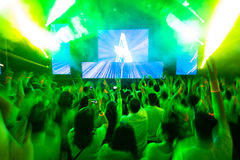 Dance club with dj. Young people dancing, clapping, happy, hands up in a laser light show and acid music, plays the famous DJ. In green tones Stock Photography